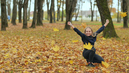 A young girl schoolgirl throws autumn leaves in a city park. Slow motion. 写真素材