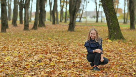 A teenage girl is sitting in an autumn park. 写真素材