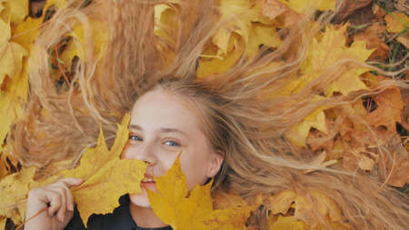 Young happy girl lies in autumn leaves and poses with maples leaves.