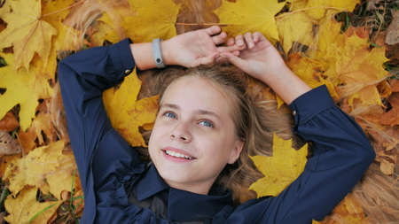 A young happy girl lies in the autumn leaves.