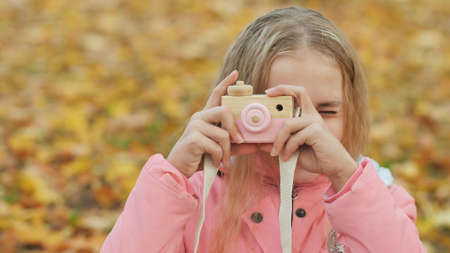 Teenage girl with toy cameras takes pictures in the autumn park. 写真素材