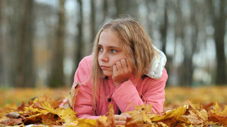 A little girl indifferently lies on the autumn foliage in a city park. She is very sad. 写真素材