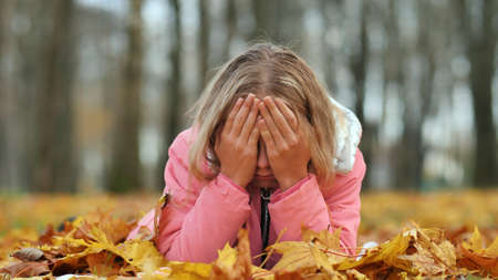 Teenage girl crying in the autumn foliage in the park. 写真素材
