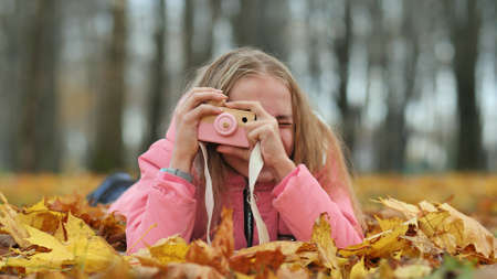 A teenage girl with a toy camera takes pictures of lying in the autumn foliage in the park.