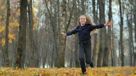 Happy teenage girl runs in the autumn park.