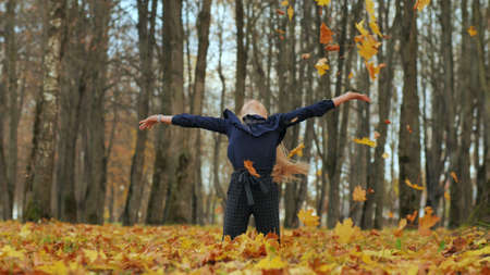 A young girl schoolgirl throws autumn leaves in a city park. 版權商用圖片