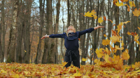 A young girl schoolgirl throws autumn leaves in a city park. 写真素材