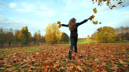 A young girl schoolgirl runs and scatters autumn leaves in a city park. 写真素材