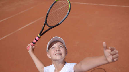 A young tennis player serves in a tennis game.