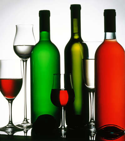 Three wine bottles and four glasses. White, red and rose wine.
