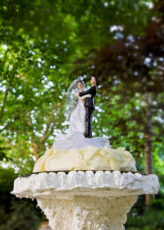 Little dolls (brige and groom) on wedding cake. photo