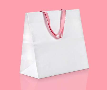 White shopping bag on pink. photo