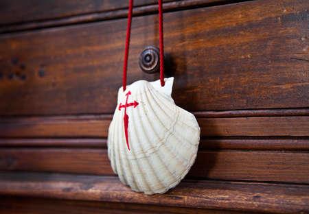 way of st james: Shell with red cross, souvenir of the camino de Santiago de Compostela, Galicia, Spain. Stock Photo