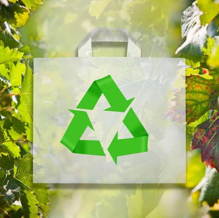 Zak met recycle symbool op groene bladeren. Stockfoto