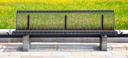 confortable: Park bench in spring with yellow flowers on background. Stock Photo
