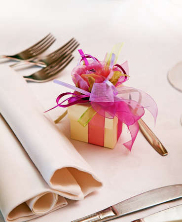 confetto: Little box (bomboniera) for guest attending the wedding on the setting table. Stock Photo
