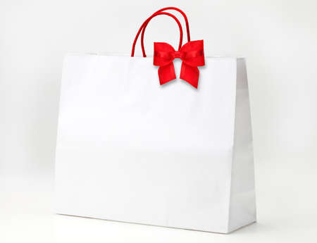 White shopping bag with red bow on white.