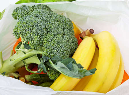 Open plastic bag with fruits and vegetables photo