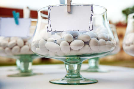 confetto: Candies in a goblet with blank label. Stock Photo