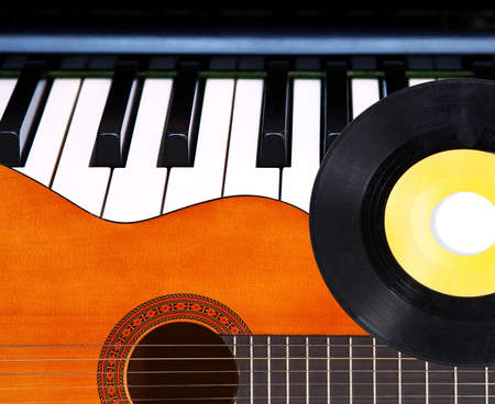 Acoustic guitar, piano keys and vinyl record. photo