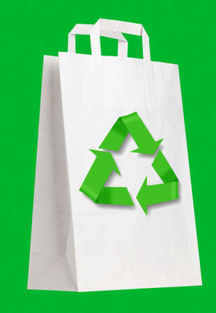 White shopping bag with recycle symbol on green. photo