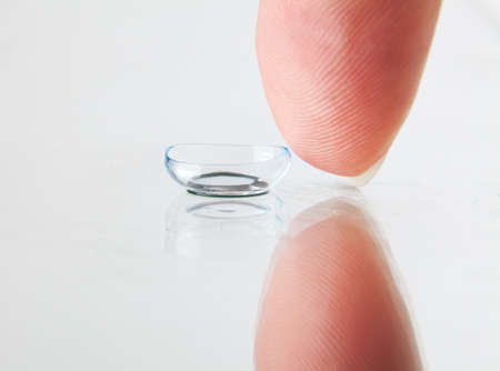 Detail of soft contact lens and finger