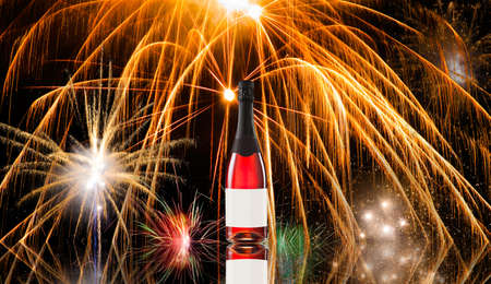 Fireworks against a black sky and wine bottle photo