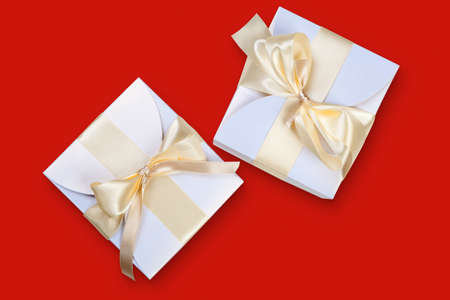 Two boxes with gold ribbon on red photo