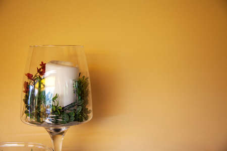 romatic: Rustic decor (glass with candle and flower) near yellow wall (with sopace for your text or logo)