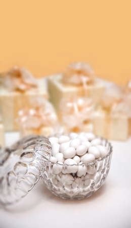 Candies in a glass bowl, yellow background (wedding reception)