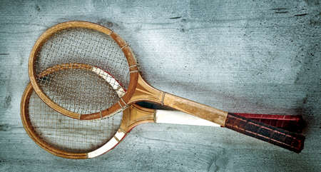 Two vintage tennis rackets on wooden background (vintage effect)