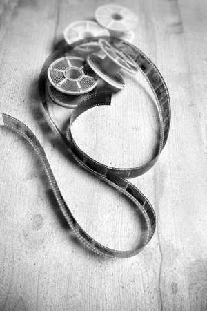 darkroom: White and black photographic film and old photographic tools on grey background