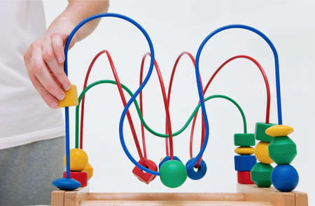 Wooden multicolored toy. Labirinth educatonal game with adult hand