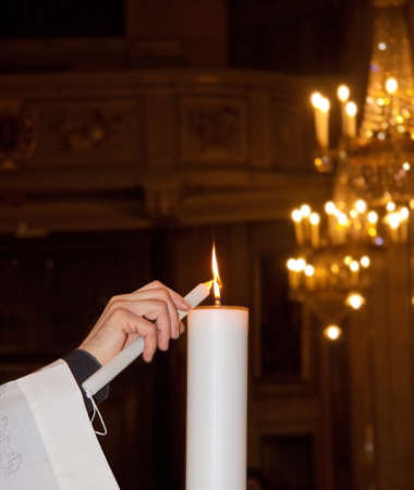 Ein katholischer Priester zündet während einer Taufe in einer italienischen Kirche eine Kerze an