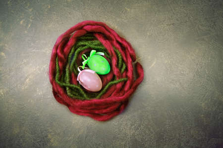 Red and green woolen nest with Easter eggs on dark background Imagens