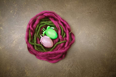 Violet and green woolen nest with Easter eggs on dark background