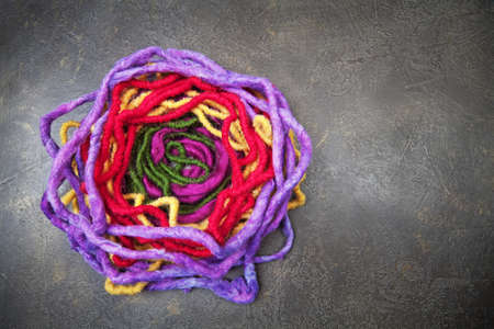 Violet, red, yellow and green woolen nest on  background