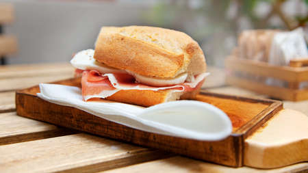 Ham and mozzarella sandwich on a wood chopping board. Selective focus. Imagens