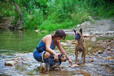 Young woman with her dogs in a small strem in the North of Italy, Piedmont.