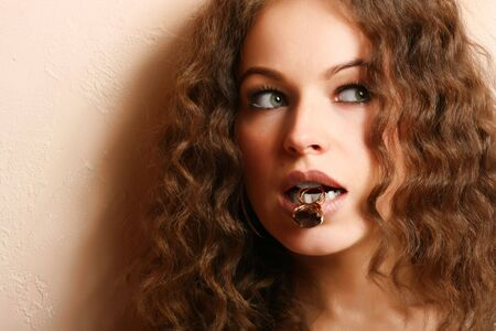 Jewelry and Beauty. Beautiful woman holding a ring in a teeth Stock Photo - 3860436