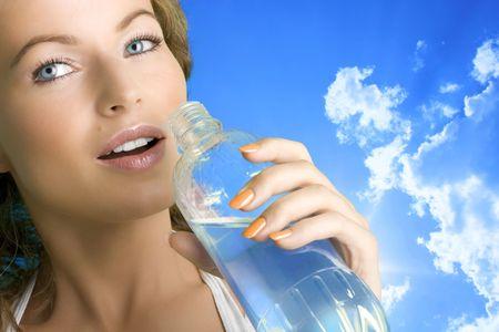 Beautiful girl drinking water outdoors photo