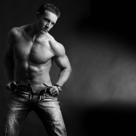 masculine: Beautiful young man posing on dark background