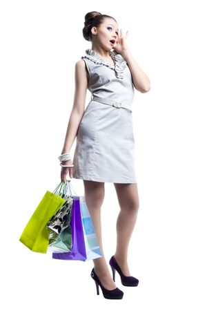Portrait of young beautiful women with her shopping bags. Isolated on white background