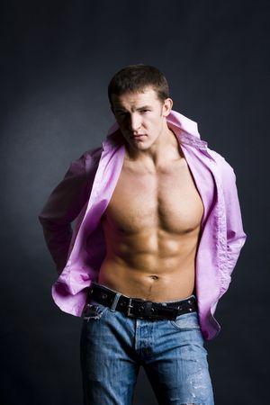 Beautiful young man posing on dark background photo
