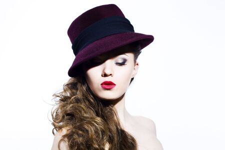 Beautiful young model in hat on the white background. Contrast photo