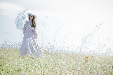 Beautiful woman in vintage dress walking across a field photo