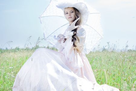 Beautiful woman in vintage dress sitting in a field photo
