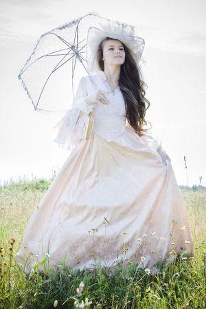 Beautiful woman in vintage dress walking across a field Stock Photo - 7525756