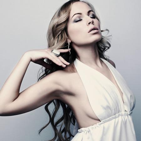 portrait of beautiful elegant blond woman in white dress photo