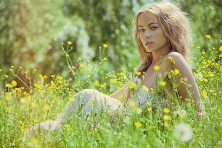 Beautiful woman outdoors enjoying nature in dress at summer meadow Standard-Bild